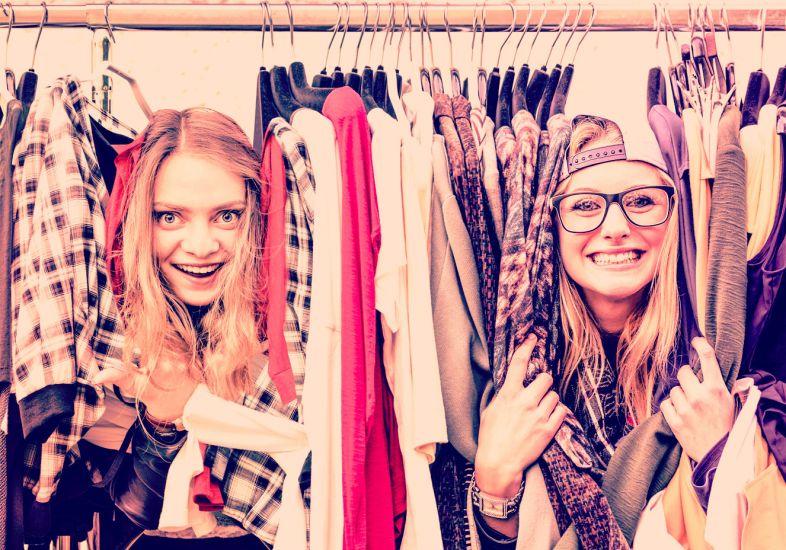 duas-garotas-sorrindo-entre-roupas-num-brecho